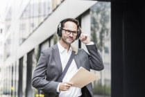 Portrait of smiling businessman with documents and headphones — Stock Photo