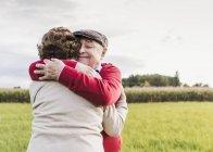 Couple sénior embrasser dans le paysage rural — Photo de stock