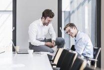 Двое смеющихся коллег в офисе — стоковое фото