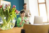 Счастливая пара смотрит на ноутбук в домашнем офисе — стоковое фото