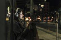 Mujer joven con auriculares esperando en la estación por la noche usando tablet - foto de stock