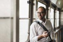 Uomo d'affari su un traghetto che guarda fuori dalla finestra — Foto stock