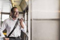 Uomo d'affari ridente su un traghetto con cellulare e auricolari — Foto stock