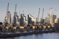 Uk, london, docklands, renovierte wohnhäuser und hafenkräne, gondeln der emirate seilbahn — Stockfoto