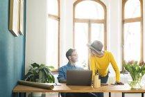 Empresario ocasional pareja en la oficina en casa trabajando en el ordenador portátil y sonriendo el uno al otro - foto de stock