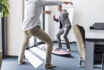 Dos colegas juguetones con tabla de surf en la oficina - foto de stock