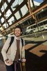 Портрет смеющегося мужчины с рюкзаком и электронным скутером в городе — стоковое фото