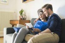 Glückliches Paar entspannt sich auf Couch mit Tablet und lacht — Stockfoto