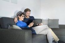 Glückliches Paar entspannt auf der Couch mit Tablet — Stockfoto