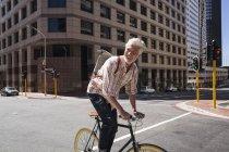 Homme mûr à vélo dans la ville — Photo de stock
