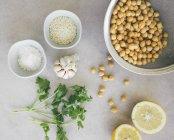 Ingredientes para guisantes hummus, garbanzos, limón, cilantro, ajo, sésamo y sal - foto de stock
