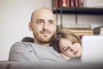 Father and daughter sitting on couch, using laptop — Stock Photo