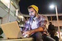 UK, London, smiling man using laptop out in the city at night — Stock Photo