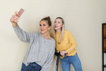 Girlfriends taking smartphone selfies — Stock Photo