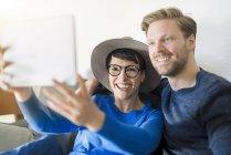 Glückliches Paar beim Selfie mit Tablet im Wohnzimmer — Stockfoto