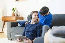 Casual Paar mit Kopfhörern entspannt auf Lounge-Couch in ihrem modernen Wohnzimmer — Stockfoto