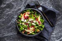 Bowl of mixed salad with lamb's lettuce, feta, pear, pomegranate seed and walnuts — Stock Photo