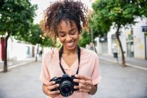 Lächelnde junge Frau blickt in der Stadt in die Kamera — Stockfoto