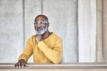 Портрет уверенного зрелого бизнесмена, сидящего за столом в офисе — стоковое фото