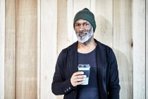 Портрет уверенного взрослого бизнесмена с кофе на вынос у деревянной стены — стоковое фото