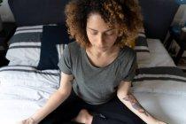 Женщина практикует йогу, сидит на кровати, медитирует — стоковое фото