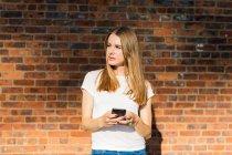 Jeune femme devant un mur de briques, en utilisant un smartphone — Photo de stock