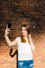 Jeune femme devant un mur de briques, prenant selfie smartphone — Photo de stock