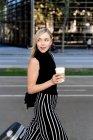 Retrato de mujer rubia sonriente con café para llevar y equipaje de ruedas - foto de stock