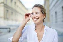 Портрет усміхненої жінки у білій сорочці та окулярах у місті. — стокове фото