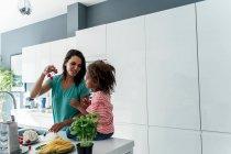 Мать и дочь готовят на кухне вместе — стоковое фото