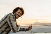 Портрет смеющегося мужчины со смартфоном на закате, Барселона, Испания — стоковое фото