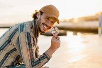 Портрет смеющегося человека, поедающего пончик на закате — стоковое фото