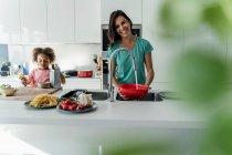 Счастливая мать и дочь готовят на кухне вместе — стоковое фото