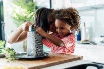 Счастливая мать и дочь готовят на кухне вместе тертый сыр — стоковое фото