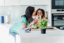 Мать и дочь готовят на кухне вместе, играя с деревянными ложками — стоковое фото