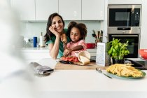 Портрет счастливой матери и дочери, готовящих вместе на кухне — стоковое фото