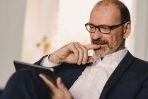 Портрет уверенного зрелого бизнесмена с помощью планшета — стоковое фото