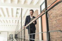Young businessman standing on gallery in modern office building, using digital tablet — Stock Photo