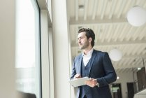 Successful manager standing in modern office building, using laptop, looking out of window — Stock Photo