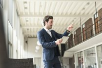 Successful manager standing in modern office building, using laptop, pointing — Stock Photo