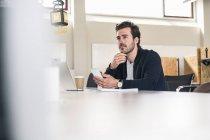 Молодий бізнесмен, який сидить на посаді, користуючись ноутбуком і смартфоном. — стокове фото