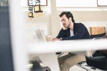 Перевтомлений бізнесмен сидить на роботі, спить перед ноутбуком. — стокове фото