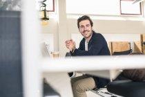 Молодий бізнесмен, який сидить на роботі з ноутбуком. — стокове фото