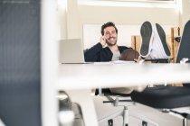 Молодий бізнесмен, який сидить в офісі, з ногами на столі, розмовляє по телефону. — стокове фото