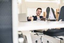 Молодий бізнесмен сидить в офісі, з ногами на столі, п