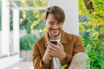 Портрет смеющегося человека, смотрящего на мобильный телефон — стоковое фото