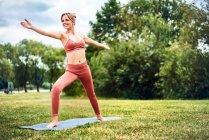 Женщина практикующая йогу в парке — стоковое фото