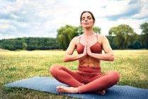Женщина практикующая йогу в парке медитирует — стоковое фото