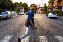 L'uomo che attraversa la strada in città — Foto stock
