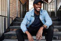 Портрет смеющегося человека, сидящего на лестнице — стоковое фото